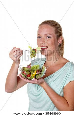 a young woman eating a fresh salad at lunch. healthy diet with vitamins.