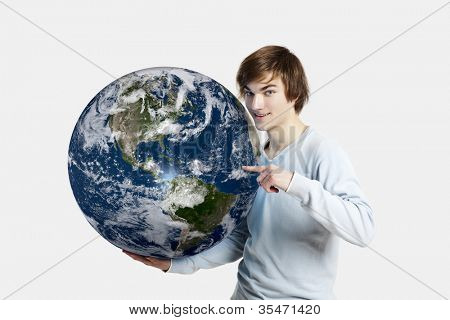 Handsome young man pointing and holding the planet earth on is hands (Elements of this image furnished by NASA)