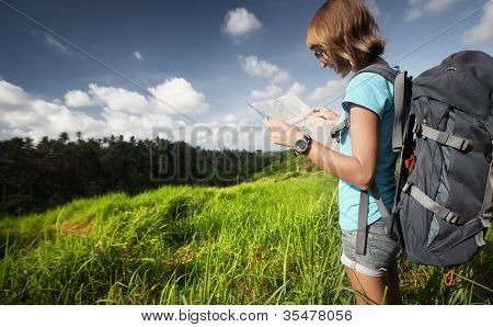 Young backpacker standing on a green meadow and looking into a map