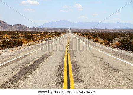 Long desert highway leading into Mojave Desert