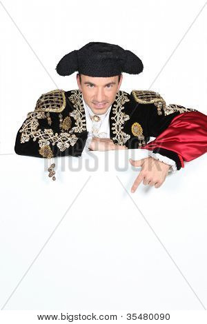 Man in a matador costume with a board blank for text or image
