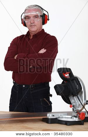 A mature carpenter with a circular saw.