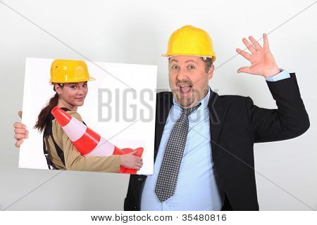 site's foreman open-mouthed holding picture of woman with construction cone
