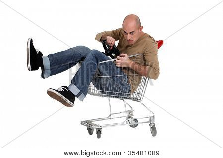 Man sat in shopping trolley with steering wheel