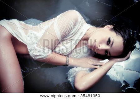 sensual beautiful woman in white wet shirt resting in water