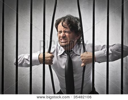 Furious strong businessman bending the bars of his prison