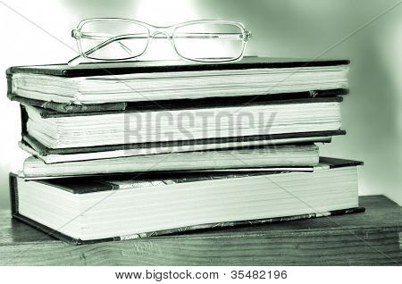 a pile of books and a pair of glasses symbolizing the concept of reading habit or studying