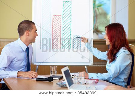 Two young colleagues argue over the graph displayed on the flip chart, conference room shoot