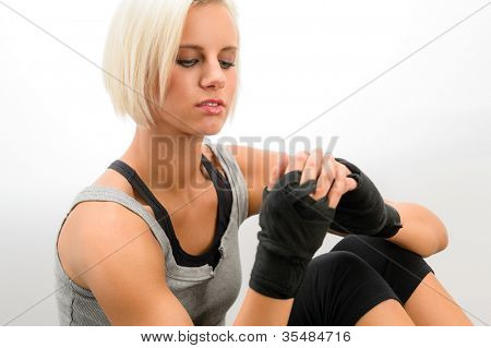 Female kickboxer wrapping wrist into protective bandages on white background