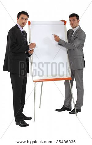 Two businessmen running through financial results
