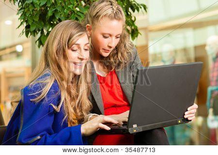 Zwei Freundinnen gehen zusammen Einkaufen und haben eine Menge SpaÃ?Â? beim Shoppen in einer Mall, sie haben ein Laptop gekauft