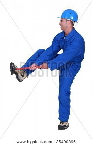 Tradesman unblocking a stoppage using a plunger