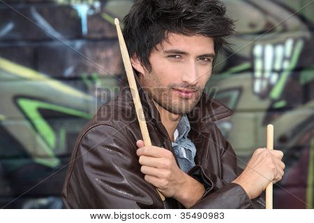Drummer standing in front of graffiti