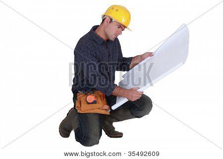 Frowning tradesman examining a blueprint
