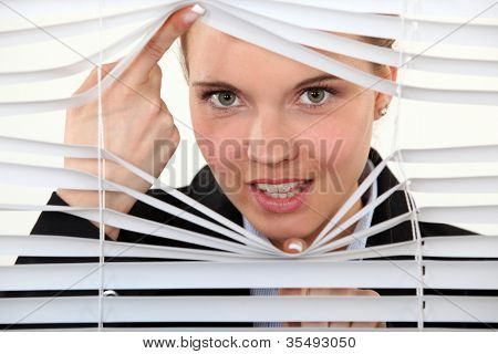 young woman behind blinds