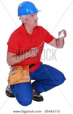 Tradesman holding a plug and a screwdriver