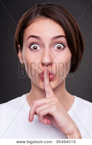 portrait of pretty woman making silence sign over dark background