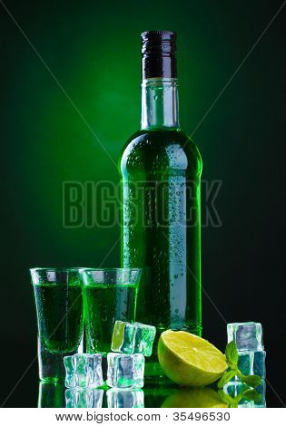 bottle and glasses of absinthe with lime and ice on green background