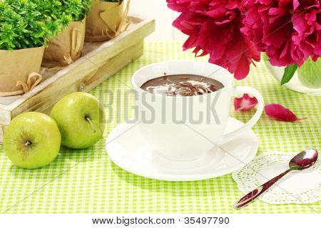 cup hot chocolate, apples and flowers on table in cafe