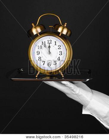 Mano en guante con bandeja de plata con despertador aislada en negro