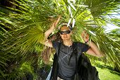 stock photo of bagpack  - young male tourist at sun glasses with bagpack in tropical jungle - JPG