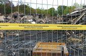 stock photo of asbestos  - yellow asbestos warning tape surrounding a burned restaurant - JPG