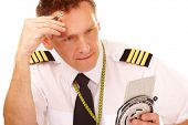 Airline pilot wearing shirt with epaulets and tie using flight computer for navigation calculations,