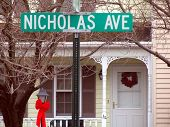 image of front door  - street sign, nicholas ave., in front of decorated townhouse ** Note: Slight blurriness, best at smaller sizes - JPG
