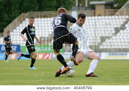 KAPOSVAR, HUNGARY - APRIL 27: Pedro Sass (in white) in action at a Hungarian National Championship soccer game - Kaposvar (white) vs Szombathely (black) on April 27, 2013 in Kaposvar, Hungary.