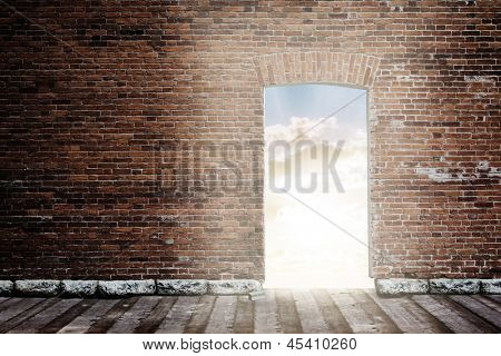 old brick wall with opened door to sunset sky