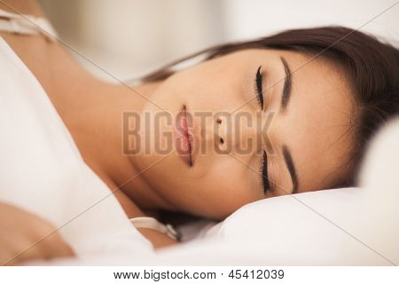 Closeup portrait of a beautiful young woman sleeping on the bed