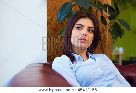 Beautiful young pensive woman sitting on the sofa and looking away at copyspace