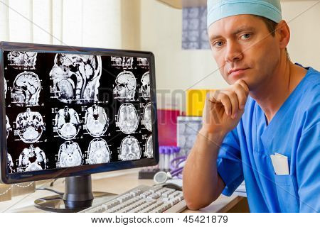 Experienced doctor with an MRI scan of the Brain on Monitior