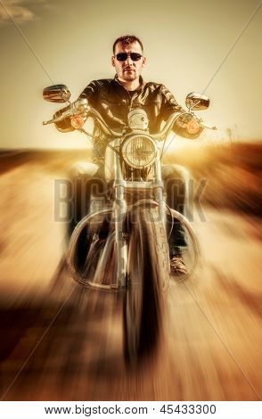 Biker in a leather jacket riding a motorcycle on the road