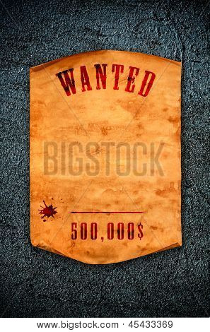 Vintage wanted poster with curled edge hanging on the wall.
