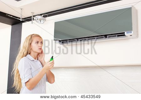 Woman looks at a broken air conditioner