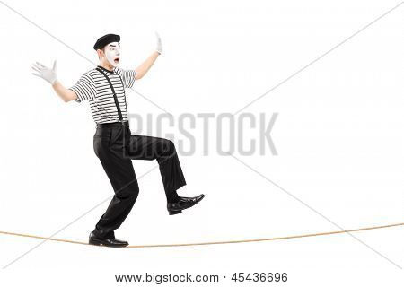 Full length portrait of an excited male mime artist walking on a rope, isolated on white background