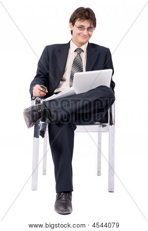 Young Businessman Looks Laptop And Calling By Cellular Phone