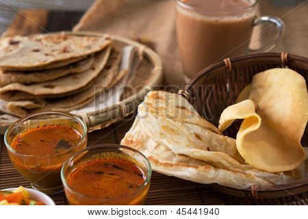 Roti canai, Chapati or Flat bread, teh tarik or milk tea and curry, famous Malaysian Indian food.
