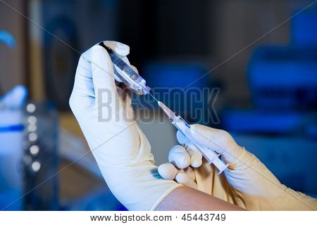 Scientist With Syringe Sucking Vaccine, Two Hands