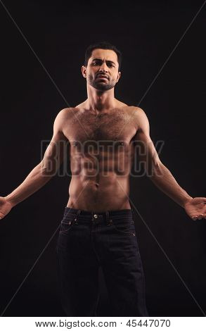 Shirtless Man On Dark Background Gesturing
