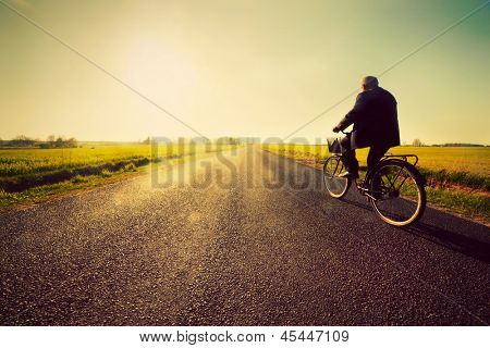 Old man riding a bike on asphalt road towards the sunny sunset sky