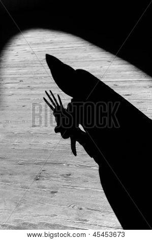 Spotlit Black Hooded Gesturing Silhouette
