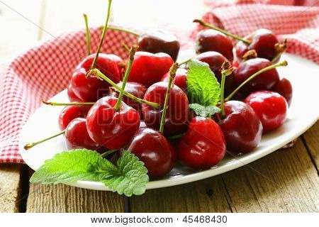 cherry berries with mint leaves on a wooden table