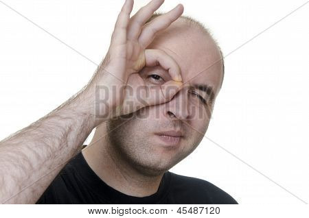 young man looking through fingers on white background