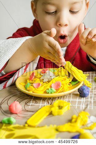 Niño jugando con el plato de Spaghetti realizado con plastilina