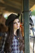stock photo of saddle-horse  - Beautiful teenage girl posing at horse ranch - JPG