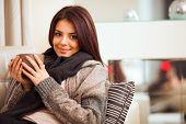 Happy young woman sitting on sofa in cozy cloths with cup of coffee