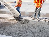 stock photo of paved road  - Pouring cement during Upgrade to urban sidewalk - JPG
