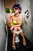 image of half naked  - girl sits in a toilet with an alcohol bottle - JPG